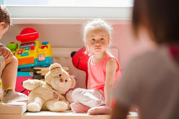 Rubia niña sentada en la sala de juegos mirando