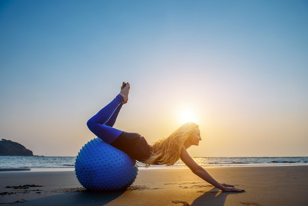 Rubia con el pelo largo hace pilates en la playa durante la puesta de sol contra el mar. mujer feliz flexible joven que hace ejercicios de la aptitud en bola azul a la luz del sol poniente.