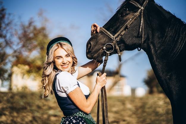 Rubia retty en vestimenta tradicional caminando con gran caballo negro al aire libre