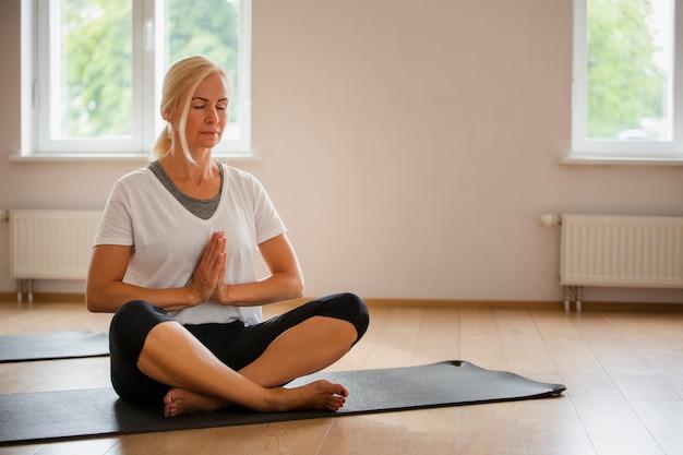 Rubia senior femenino practicando yoga