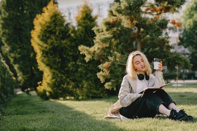 Rubia sentada en un pasto con auriculares