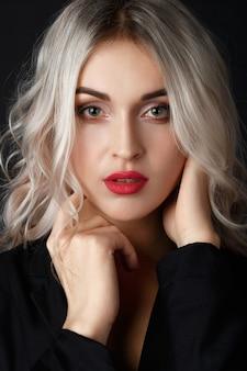 Rubia sexy con el pelo largo y rizado posa en una chaqueta negra en un estudio oscuro