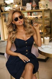 Rubia sexy en vestido corto y gafas sentado en la cafetería