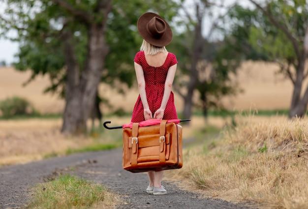 Rubia en vestido rojo con una maleta en un camino rural antes de la lluvia