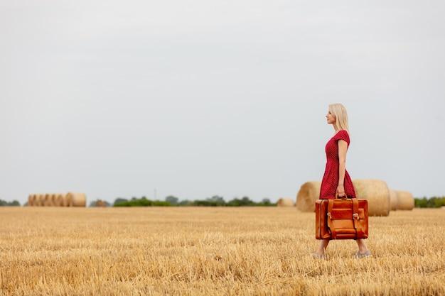 Rubia con un vestido rojo con maleta en un campo de trigo antes de la lluvia