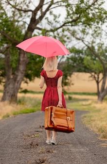 Rubia en vestido rojo con una maleta y un paraguas en un camino rural antes de la lluvia