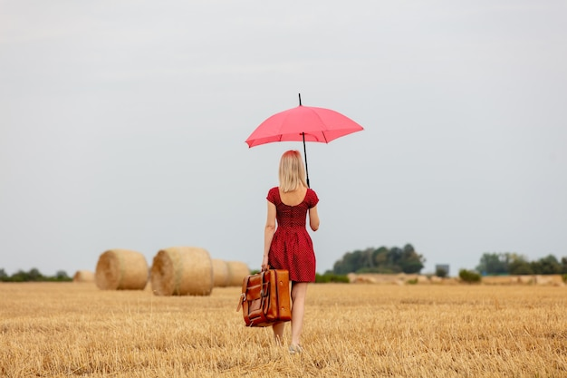 Rubia con un vestido rojo con un paraguas y una maleta en un campo de trigo antes de la lluvia