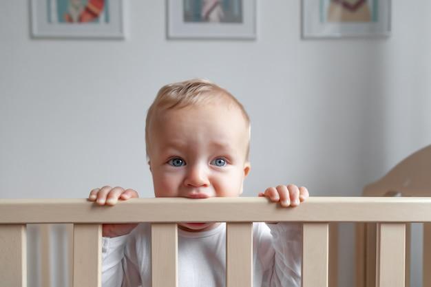Rubio lindo bebé de ojos azules en mono blanco mordiendo la cabecera de la cama de madera en el fondo del interior de la habitación de los niños modernos, espacio de copia, horizontal