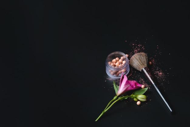 Rubor perla, flor y pincel de maquillaje sobre fondo negro