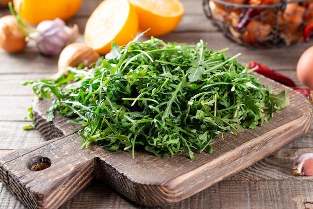 Rúcula fresca sobre fondo de madera rústica. ensalada de rúcula fresca, hojas de rúcula, rúcula, eruca o roqueta de jardín