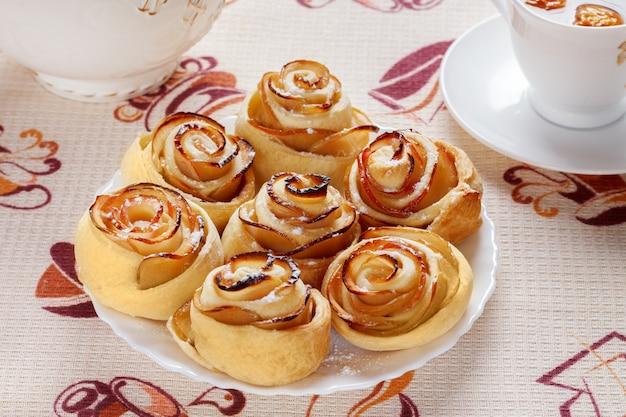 Ruddy rollos horneados en un plato blanco con una taza de té de manzana fruta