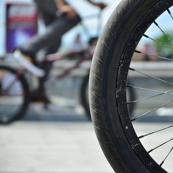 Una rueda de bicicleta bmx en el contexto de una calle borrosa con ciclistas. concepto de deportes extremos