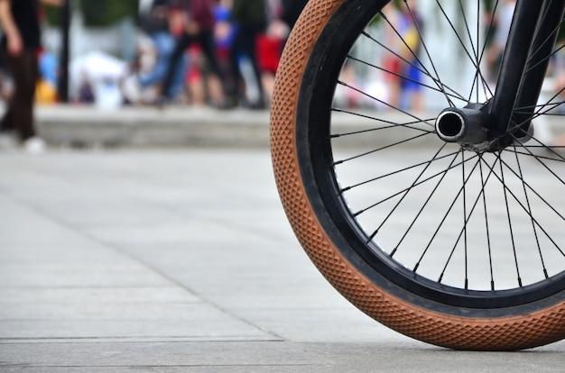 Una rueda de bicicleta bmx contra una calle borrosa con ciclistas. concepto de deportes extremos
