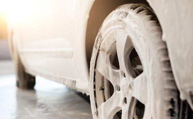 Rueda de coche bajo espuma de lavado durante el lavado de coches cerrar