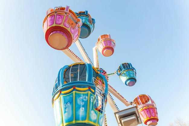 Rueda de ferris colorida con cabinas que se balancean en el cielo azul en parque de vacaciones de la diversión