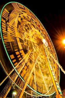 Rueda de la fortuna girando en el recinto ferial en la noche en sukhothai