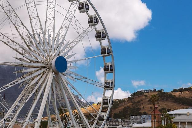 Rueda de la fortuna y vista a la montaña de la mesa en waterfront en ciudad del cabo