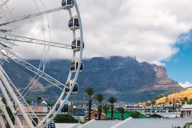 Rueda de la fortuna en waterfront en ciudad del cabo y table mountain cubierto de nubes