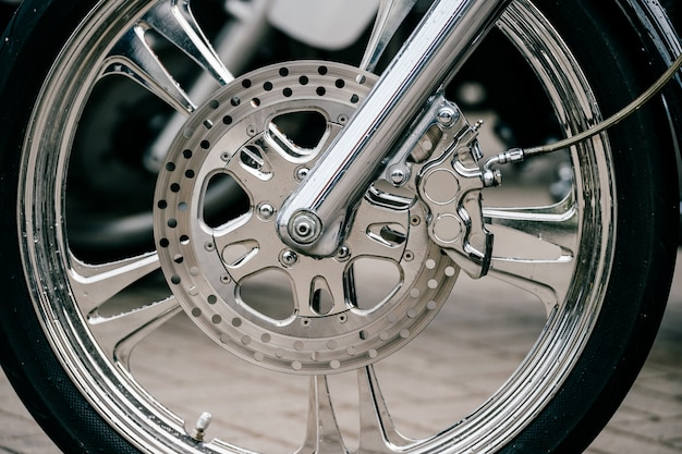 Rueda de moto con sistema de frenos de disco y radios metálicos. closeup foto detallada de motos horquillas y neumáticos.