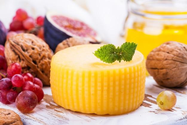 Rueda de queso amarillo con especias y aperitivos.