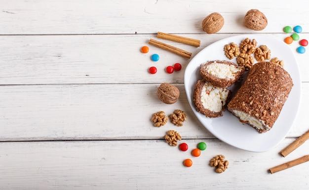 Ruede la torta con la cuajada y las nueces aisladas en el fondo de madera blanco.