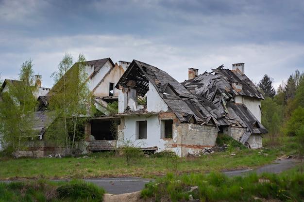 Las ruinas de una antigua casa de ladrillo con techo de madera y árboles.