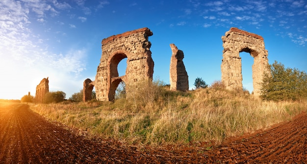 Ruinas del antiguo acueducto en appia way en roma, italia