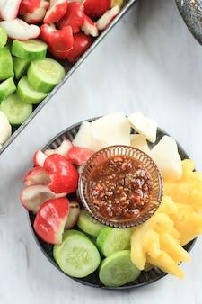 Rujak buah o plato de ensalada de frutas indonesias en rodajas, servido con salsa de azúcar morena picante y maní molido. fondo blanco