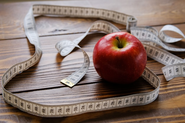 Ruleta y una manzana roja en una mesa de madera. el concepto de dieta, nutrición saludable.
