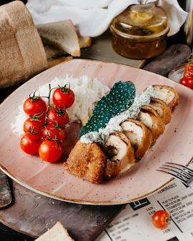 Ruletas de pollo frito con arroz y tomates.