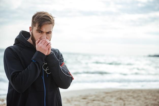Runner calentado en la playa mirando a la cámara