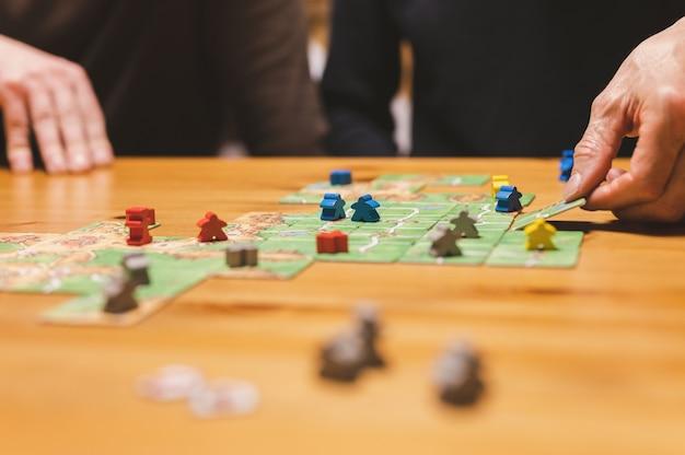 Rusia, diciembre de 2020: dos amigos hombres se divierten jugando al juego de mesa de carcassonne a última hora de la tarde o por la noche. manos masculinas y tarjetas de juego y fichas en la mesa