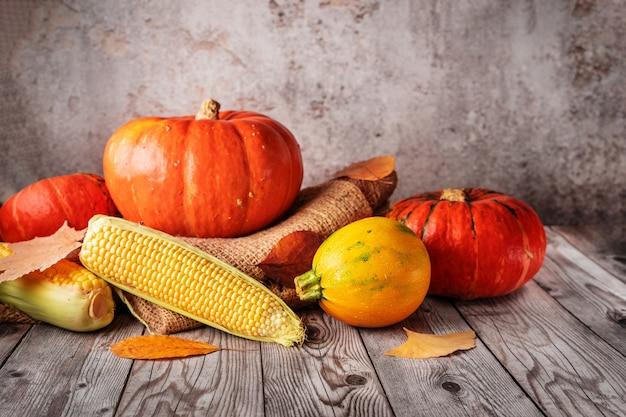 Un rústico bodegón otoñal con calabazas, calabacines y mazorcas de maíz. concepto de acción de gracias, cosecha, hallowwen y otoño