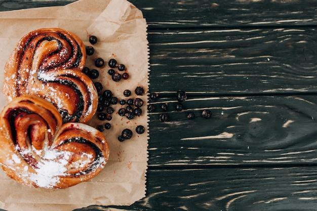 Rústico con pastel de bayas negro actual en mesa de madera negra.