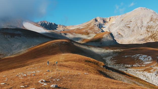 Una ruta a través de picos y colinas a través de majestuosos paisajes con turistas y viajeros en la distancia.