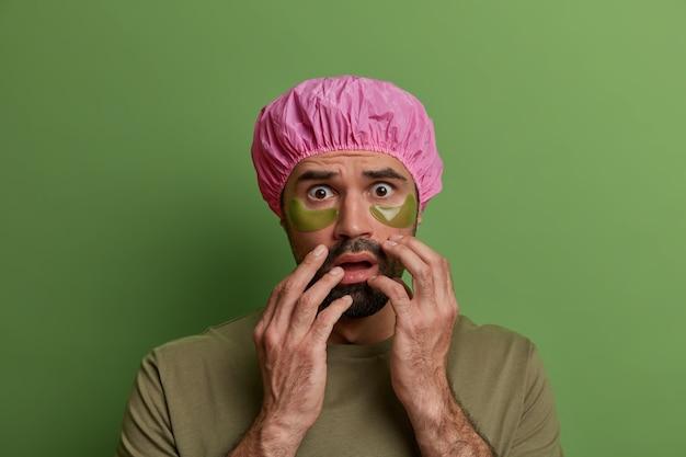 Rutina de cuidado de la piel, tratamiento facial. un chico europeo asustado usa parches de colágeno debajo de los ojos, se preocupa por la cara, usa un gorro de ducha impermeable vestido con una camiseta informal aislada en una pared brillante y vívida.