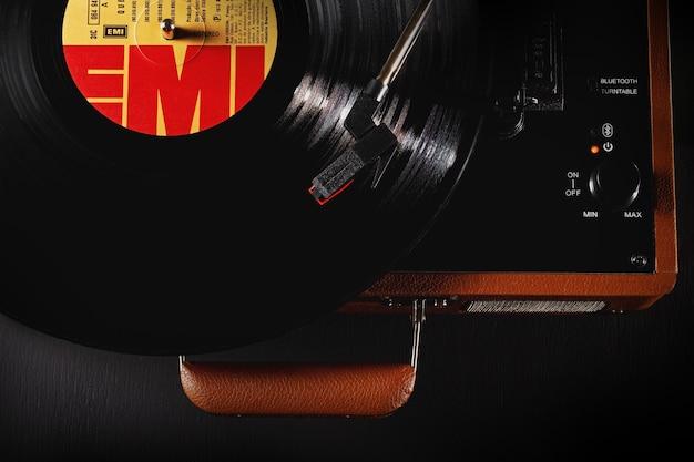 Sã £ o luãs, maranhã £ o, brasil - 23 de marzo de 2021: vista superior toca vinil discotecas de la marca raveo, con disco de vinilo de la banda de rock queen del sello emi. color marrón.