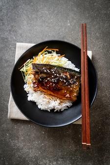 Saba pescado a la parrilla con salsa teriyaki en un tazón de arroz cubierto