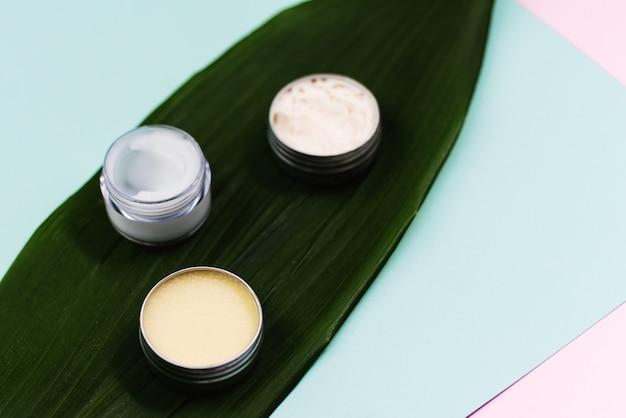 Sábana natural con cosméticos para el cuidado de la piel e hidratación de la piel de la cara y los labios. crema en un frasco de plástico y en un recipiente metálico sobre una hoja de palma