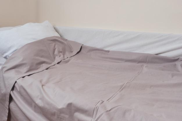 Sábanas y almohada, cama hecha para dormir