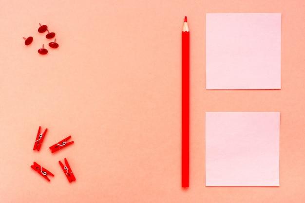 Sábanas para notas, clips y un lápiz sobre rojo.