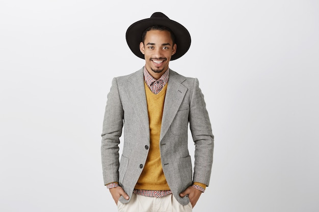 Sabe cómo hacer grandes negocios. retrato de modelo masculino guapo seguro de sí mismo con piel oscura, vestido con chaqueta y sombrero de moda, tomados de la mano en los bolsillos y sonriendo con confianza
