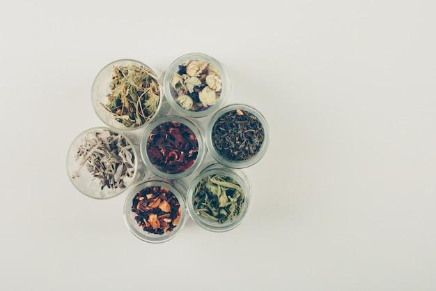 Sabores de té, hierbas secas en frascos pequeños. aplanada