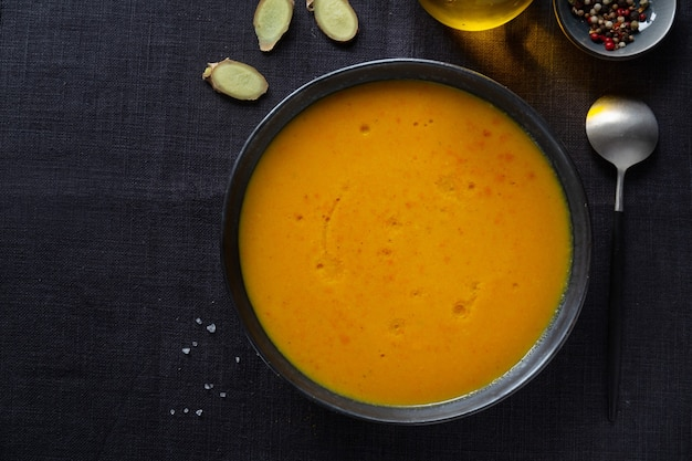 Sabrosa y apetitosa sopa de lentejas de calabaza oriental con jengibre servida en un tazón. de cerca