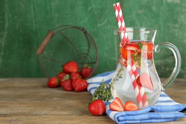 Sabrosa bebida fresca con fresas y tomillo, en madera