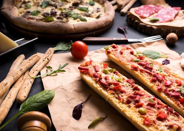 Sabrosa comida italiana con tomate cherry; palitos de pan y tenedor