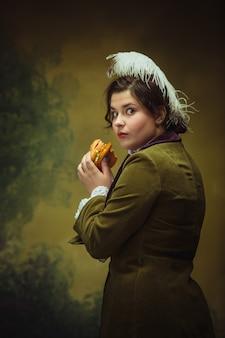 Sabrosa comida rápida. aspecto de moda moderno, retrato de mujer hermosa del período renacentista