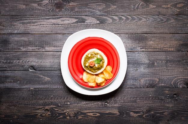 Sabrosa y deliciosa bruschetta con aguacate, tomate, queso, hierbas, papas fritas y licor, sobre un fondo de madera.
