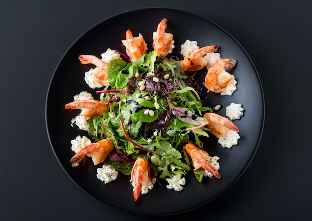 Sabrosa ensalada con camarones tigre, lechuga, ensalada y queso philadelphia en plato negro.