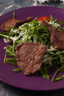 Sabrosa ensalada de ternera frita, rúcula y salsa